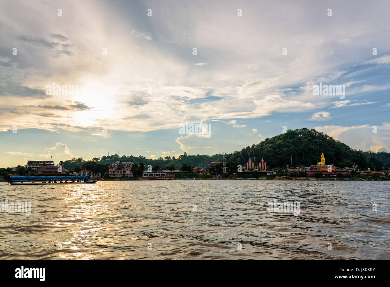 Beautiful natural landscape and tourist boat cruising the beauty of the Mekong River coast at sunset in the Golden - Stock Image