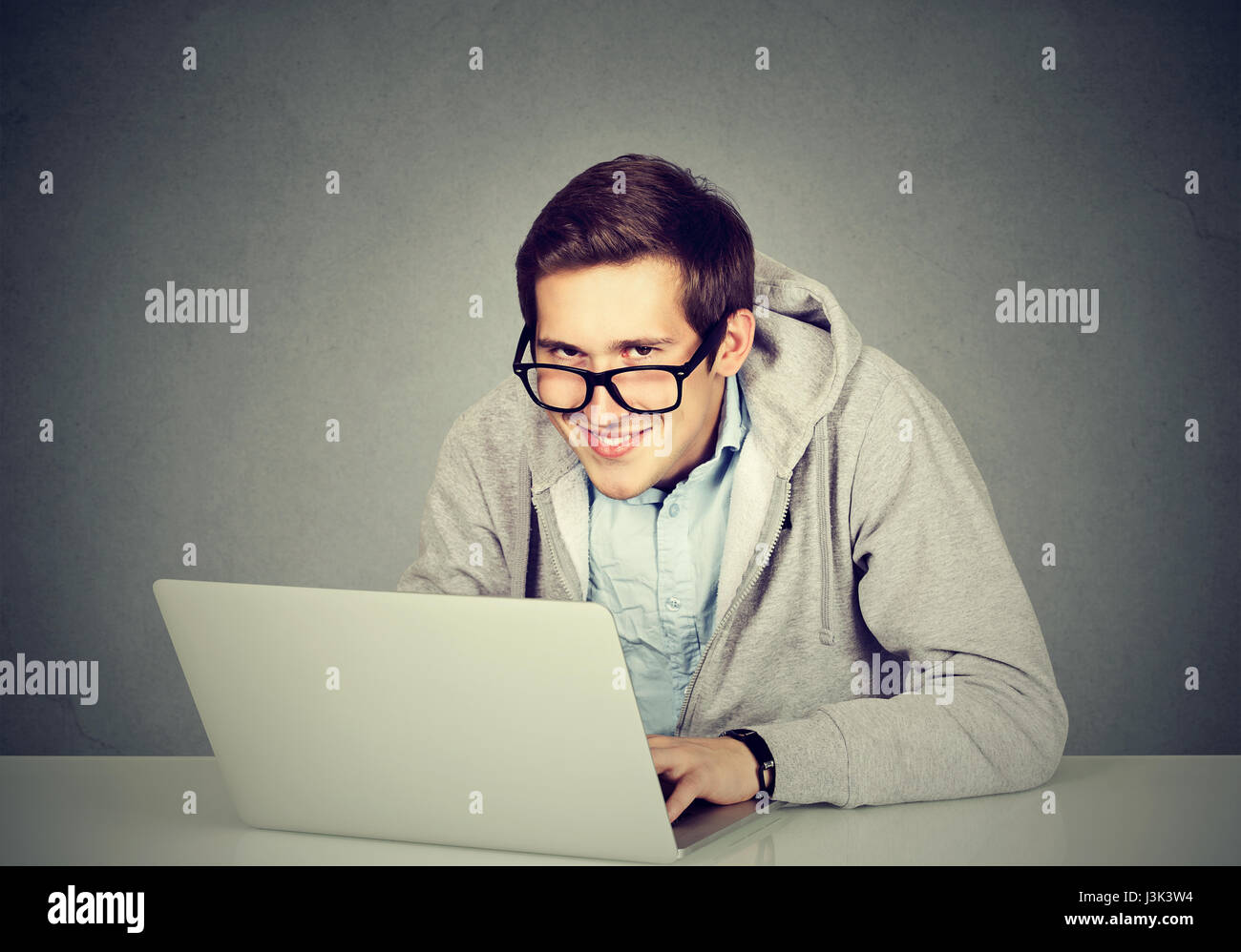 Young sly devious man using a laptop plotting server sabotage - Stock Image
