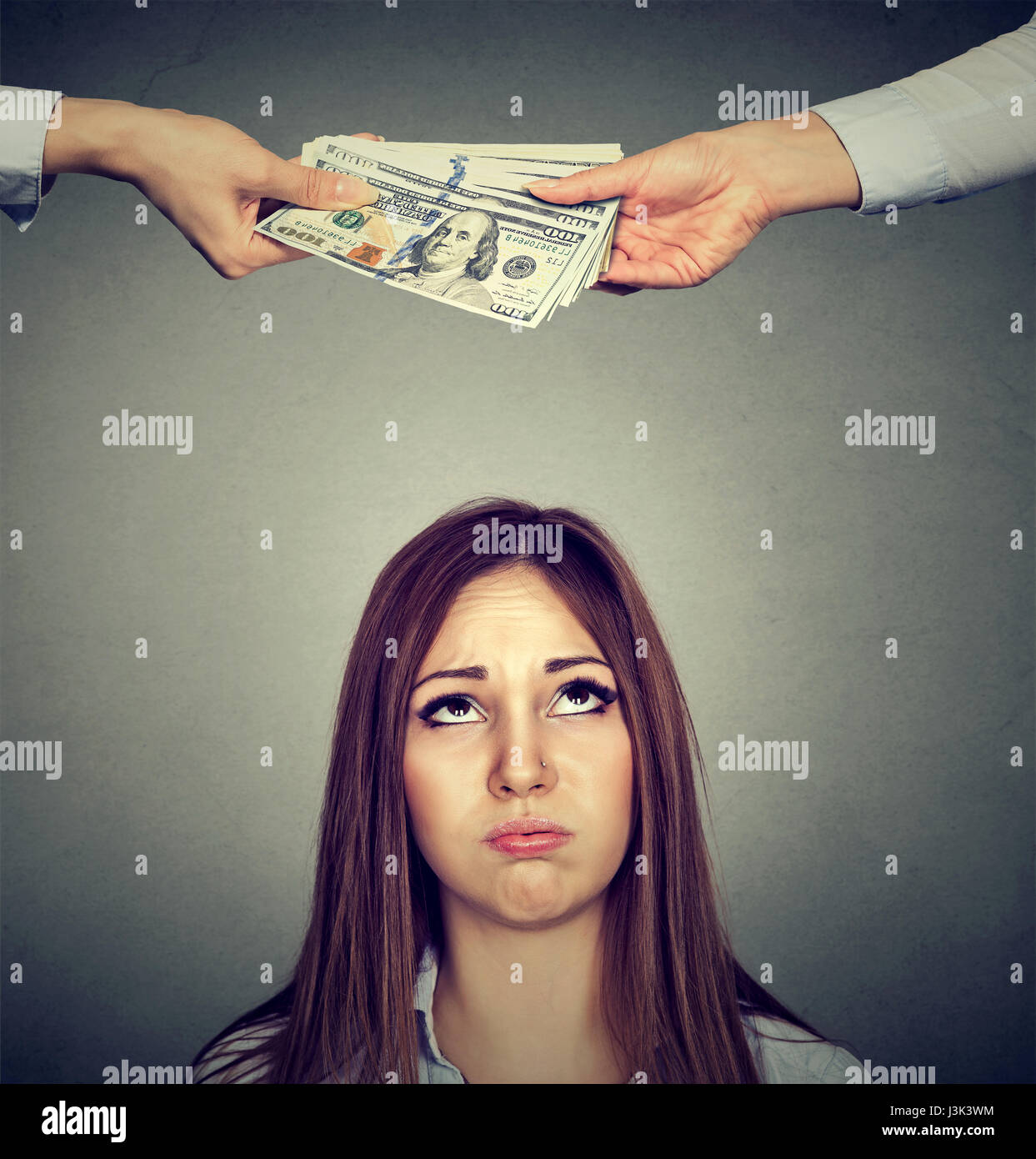 Upset worried sad woman looking up at two hands exchanging money - Stock Image