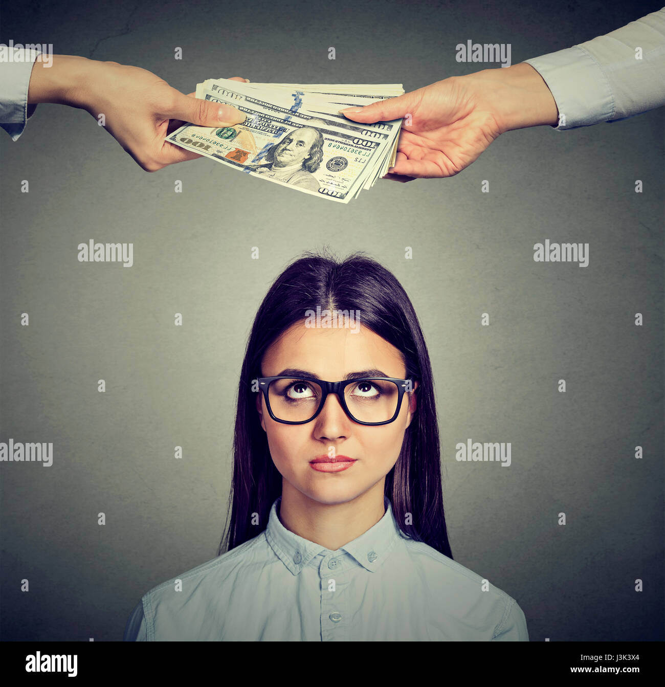 Worried sad woman looking up at two hands exchanging money - Stock Image