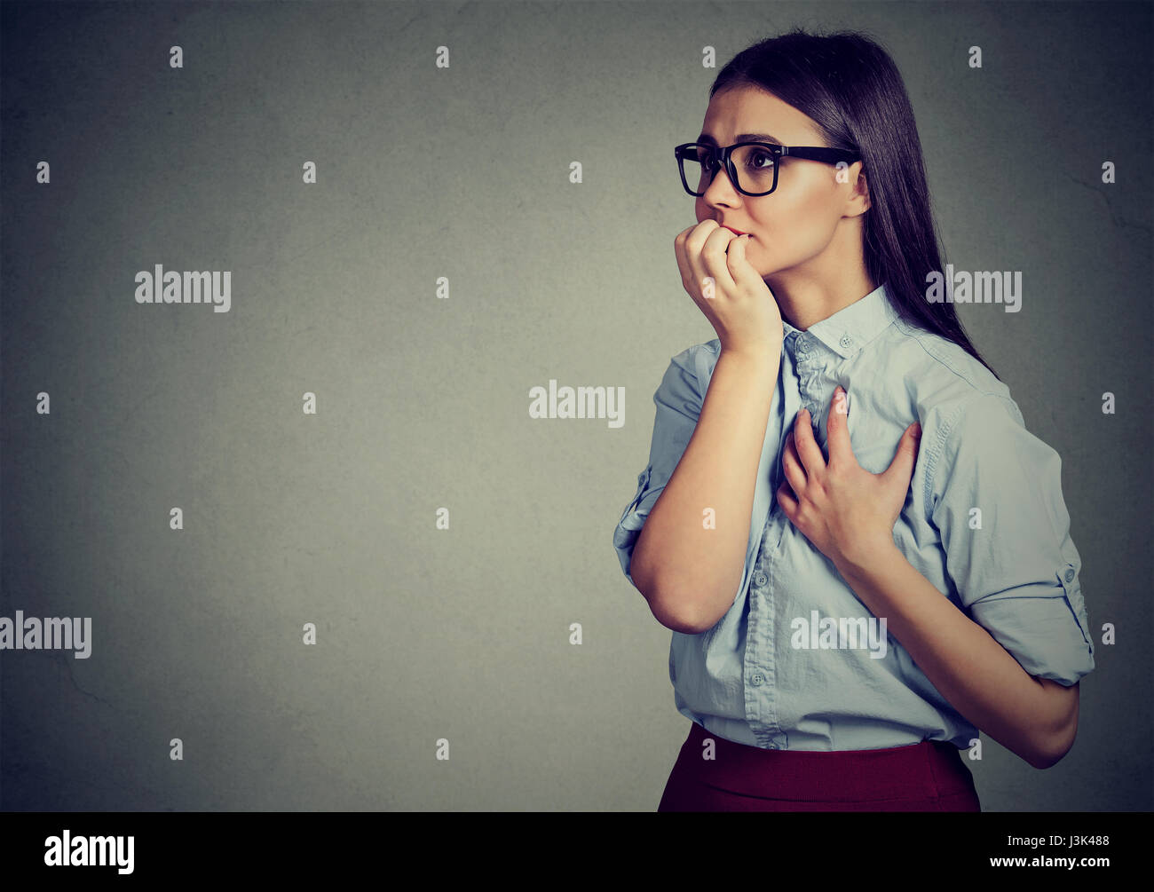 Closeup portrait unsure hesitant woman biting her fingernails craving for something or anxious isolated on gray - Stock Image