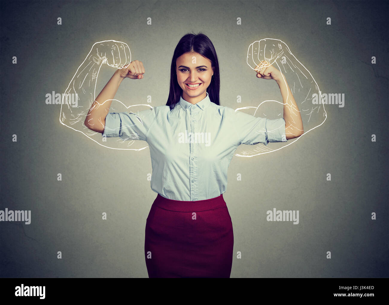 Powerful confident woman flexing her muscles isolated on gray wall background. Human face expressions, emotions - Stock Image