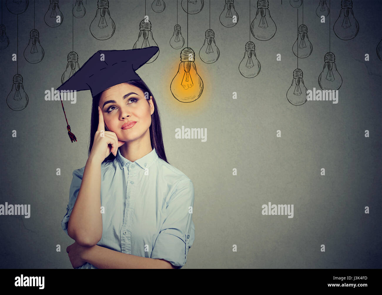 Graduate student young woman in cap gown looking up at bright light bulb thinking isolated gray wall background. - Stock Image
