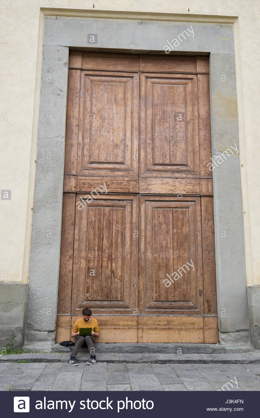 Man sitting on the stoop of the large wooden doors of St. Mary of the Holy Spirit, Basilica of Santa Maria del Santo - Stock Image