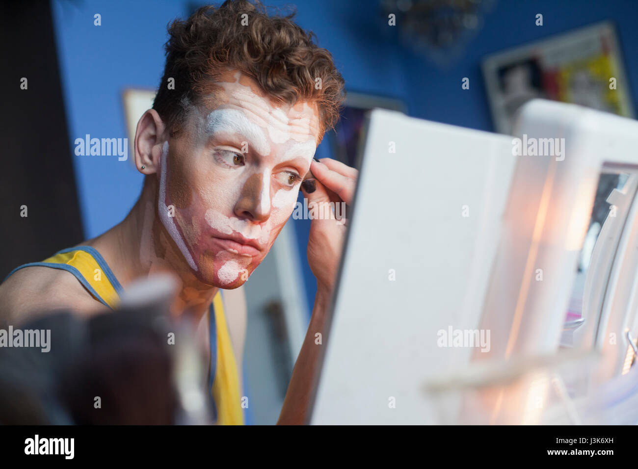 Young man applying drag makeup - Stock Image