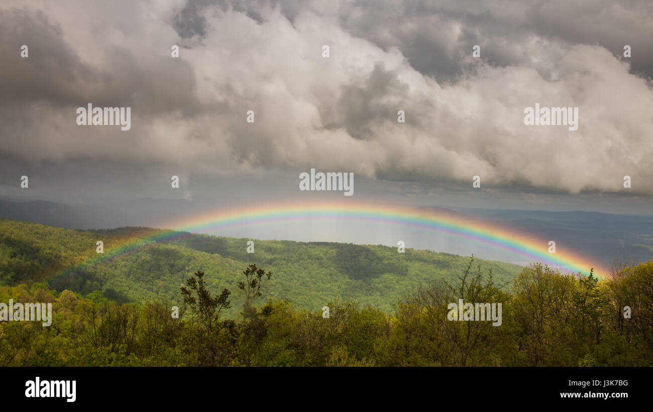Stormy and ominous skies give way to a vibrant, beautiful rainbow over the Shenandoah Valley Stock Photo