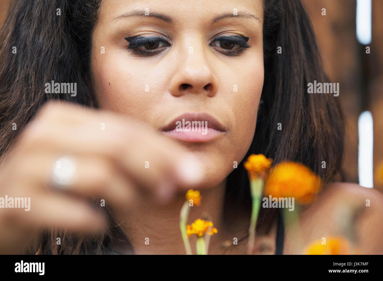 Young woman looking after orange flowers. - Stock Image