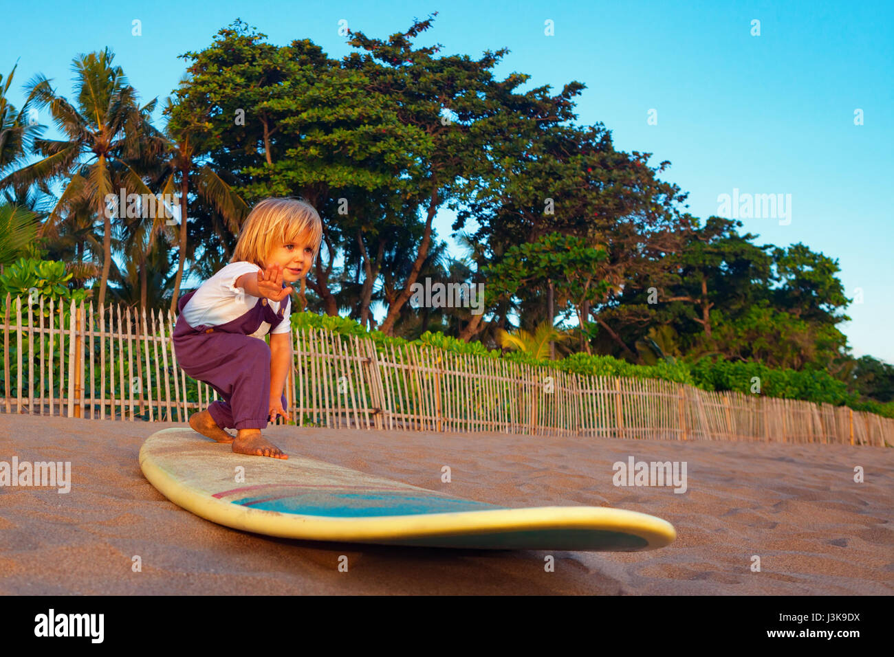 Little baby boy - young surfer stand on surf board with fun on sunset sea sand beach. Family lifestyle, people outdoor - Stock Image