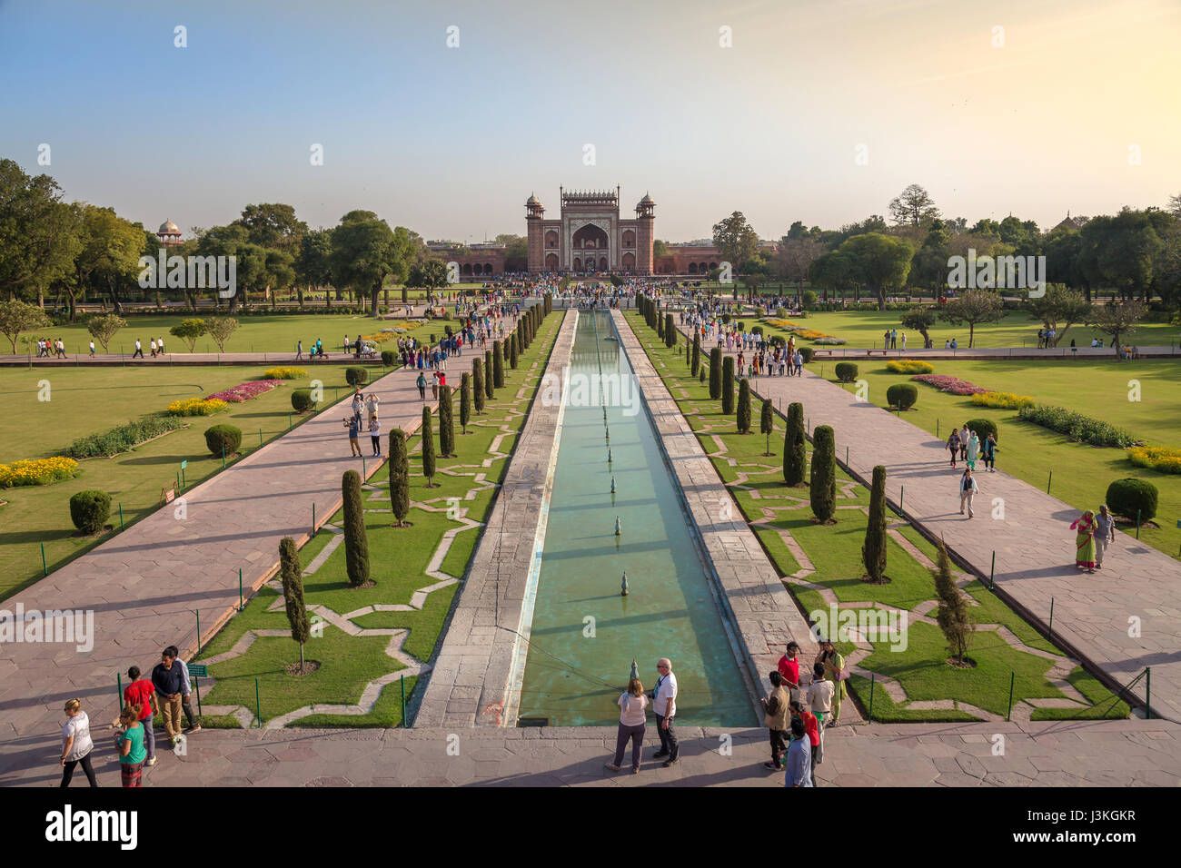 Taj Mahal garden with tourists and red sandstone built Mughal architectural East gate as viewed from the top of - Stock Image