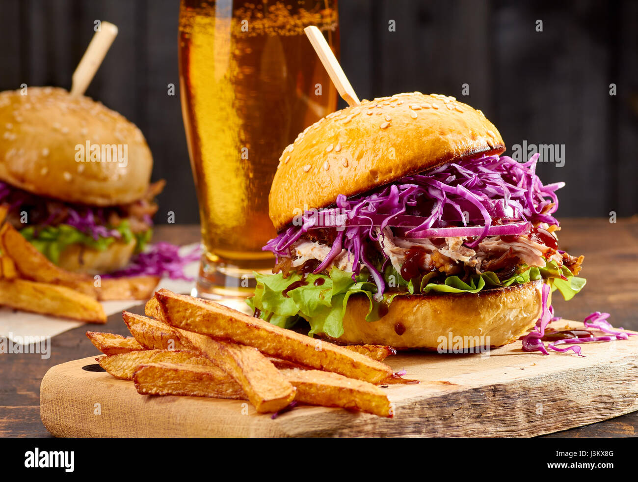 Two sandwiches with pulled pork, french fries and glass of beer on wooden background - Stock Image