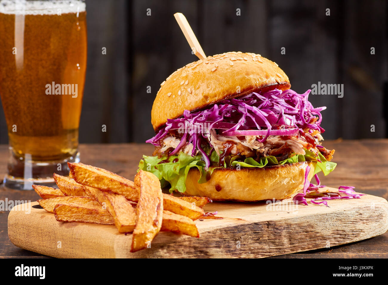 Sandwith with pulled pork and french fries on wooden background - Stock Image