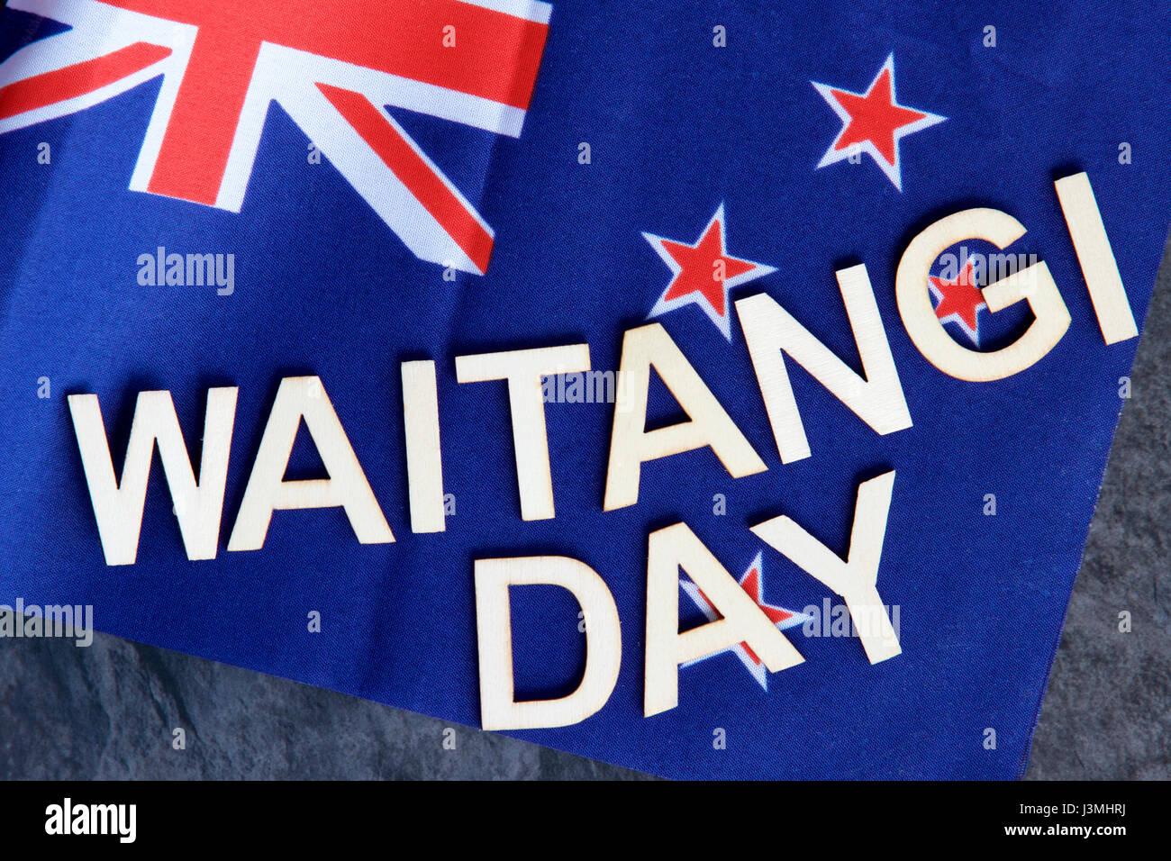Waitangi or (Independence Day) signage on a New Zealand flag. - Stock Image