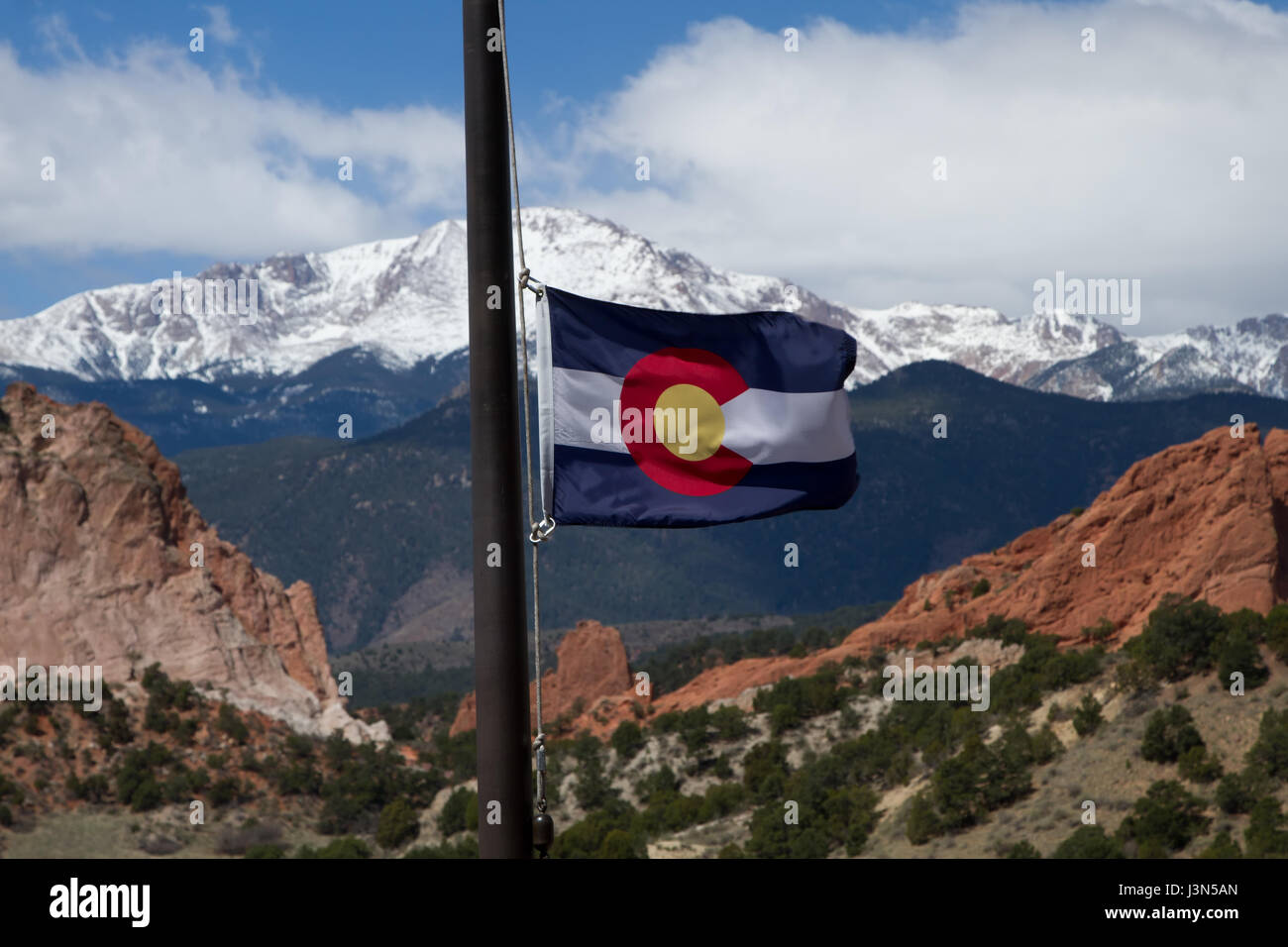 Colorado State Flag with Pikes Peak and Garden of the Gods in the background on a spring day - Stock Image