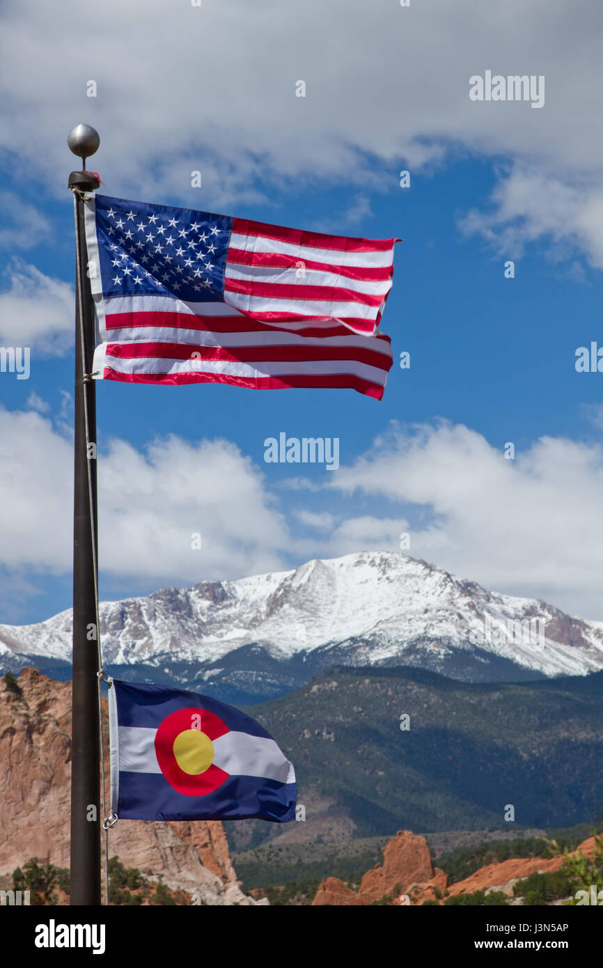American and Colorado Flag waving in the wind with Pikes Peak and Garden of the Gods in the background - Stock Image
