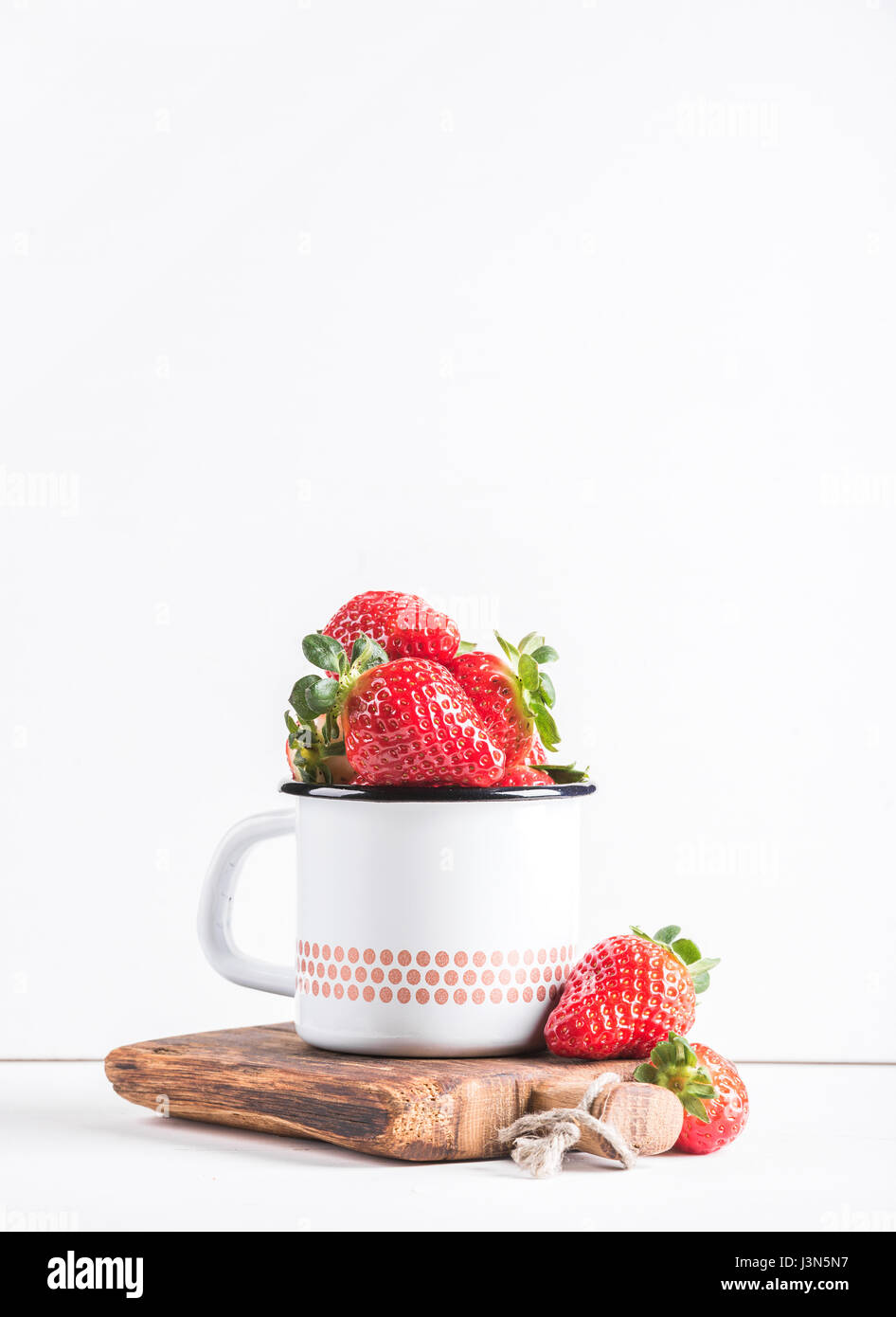 Fresh ripe red strawberries in country style enamel mug on rustic wooden board over white background - Stock Image