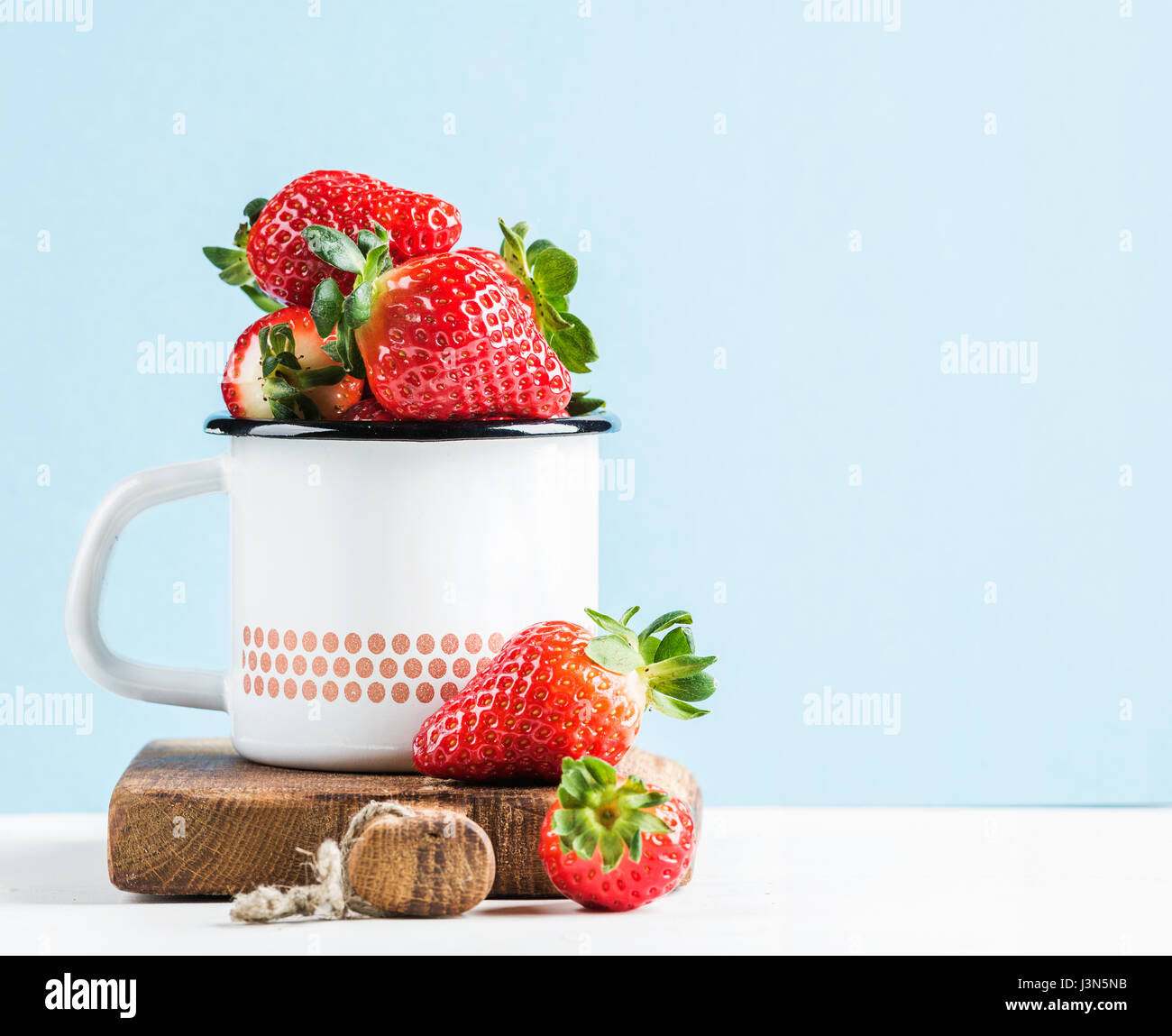 Fresh ripe red strawberries in country style enamel mug on rustic wooden board, pastel light blue background - Stock Image