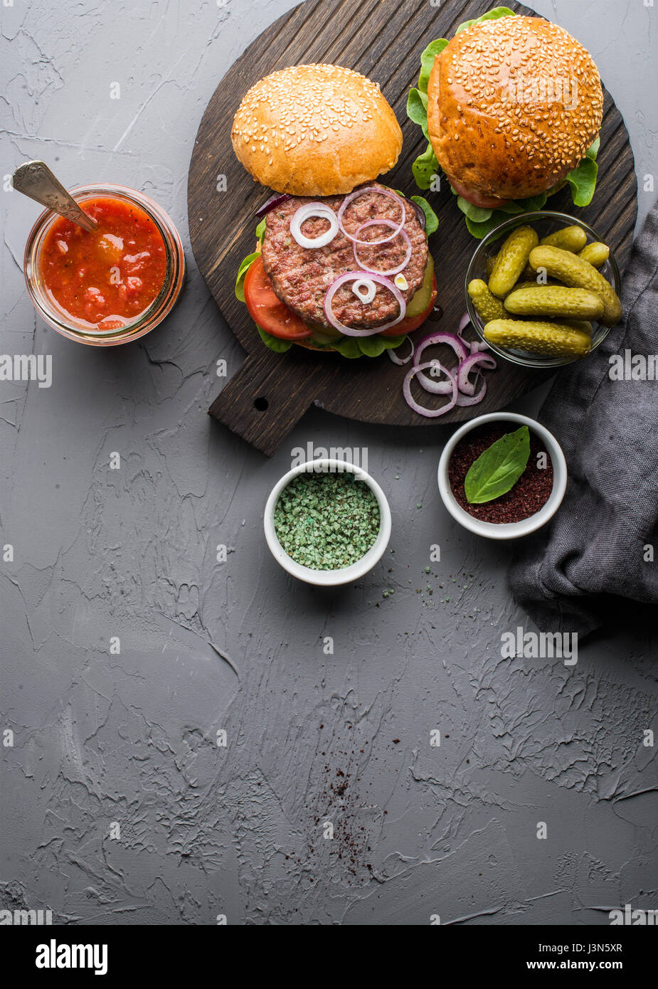 Fresh homemade burgers on dark serving board with spicy tomato sauce, green salt, pepper, pickles and onion over - Stock Image