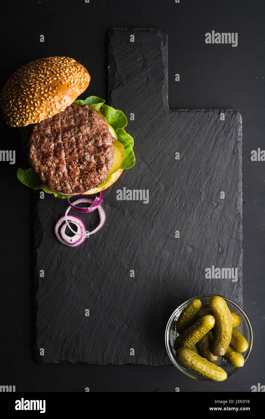 Fresh homemade burger on dark slate stone board, pickles and sliced onion over black background.  - Stock Image