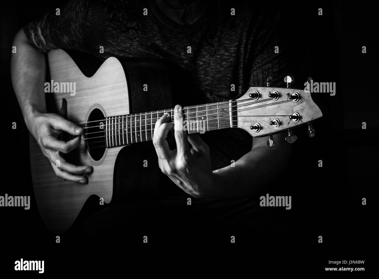 Young man with long curly hair playing an acoustic guitar. Stock Photo