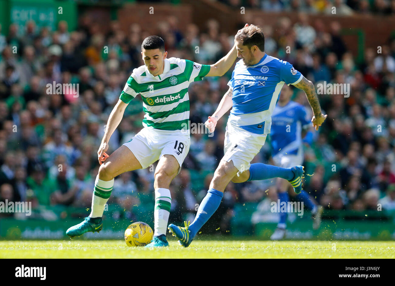 St Johnstone's Paul Paton (right) and Celtic's Tom Rogic battle for the ball during the Scottish Premiership - Stock Image