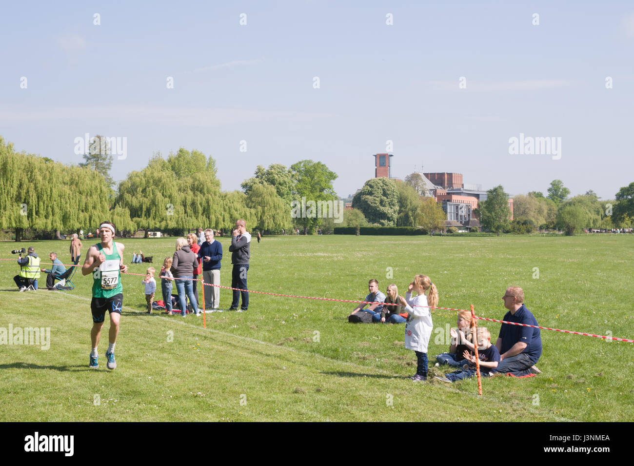 Stratford-upon-Avon, Warwickshire, UK. 7th May, 2017. A runner passing through the recreation ground with the RSC - Stock Image