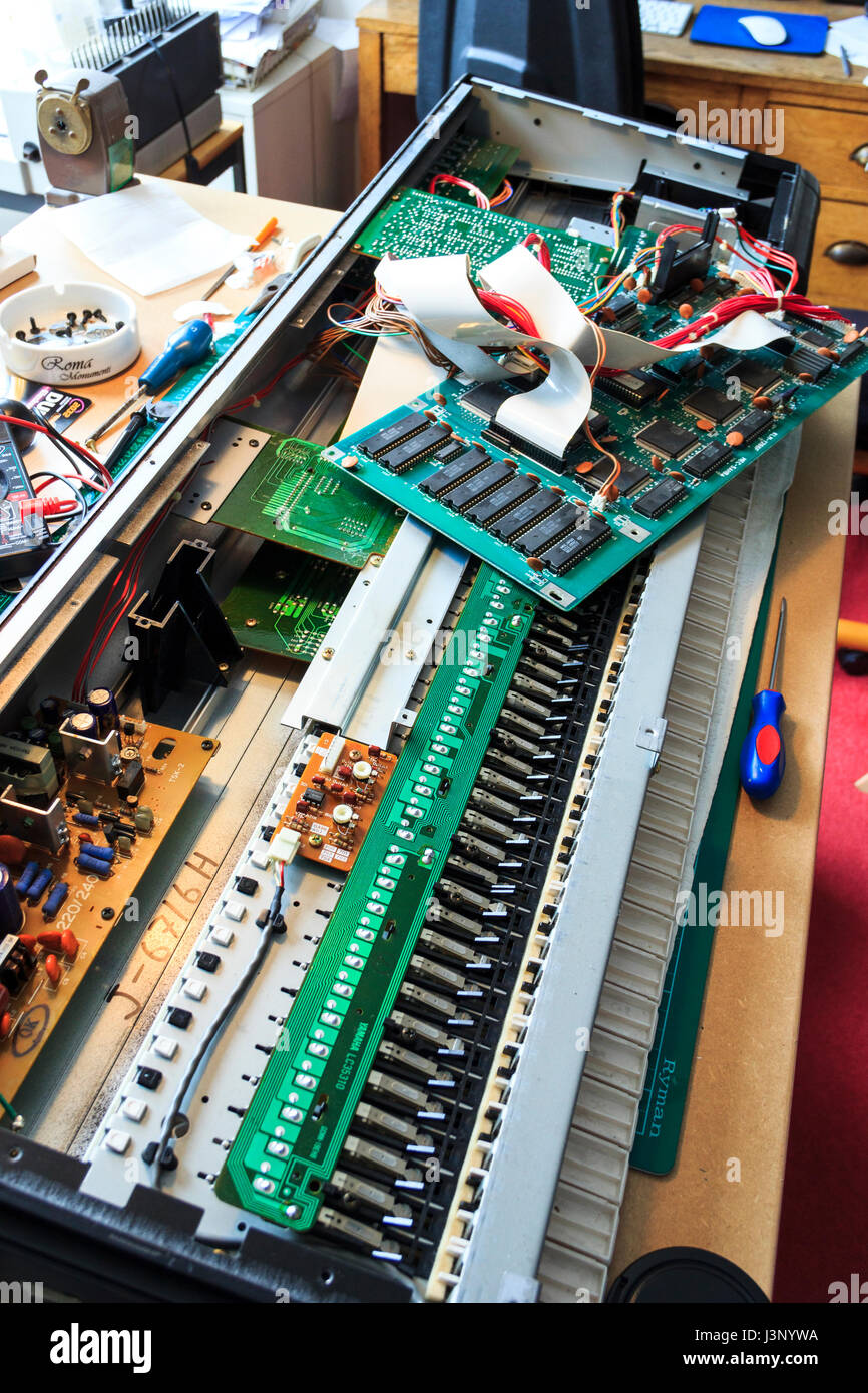 Synthesiser keyboard opened to reveal motherboard and battery housing - Stock Image