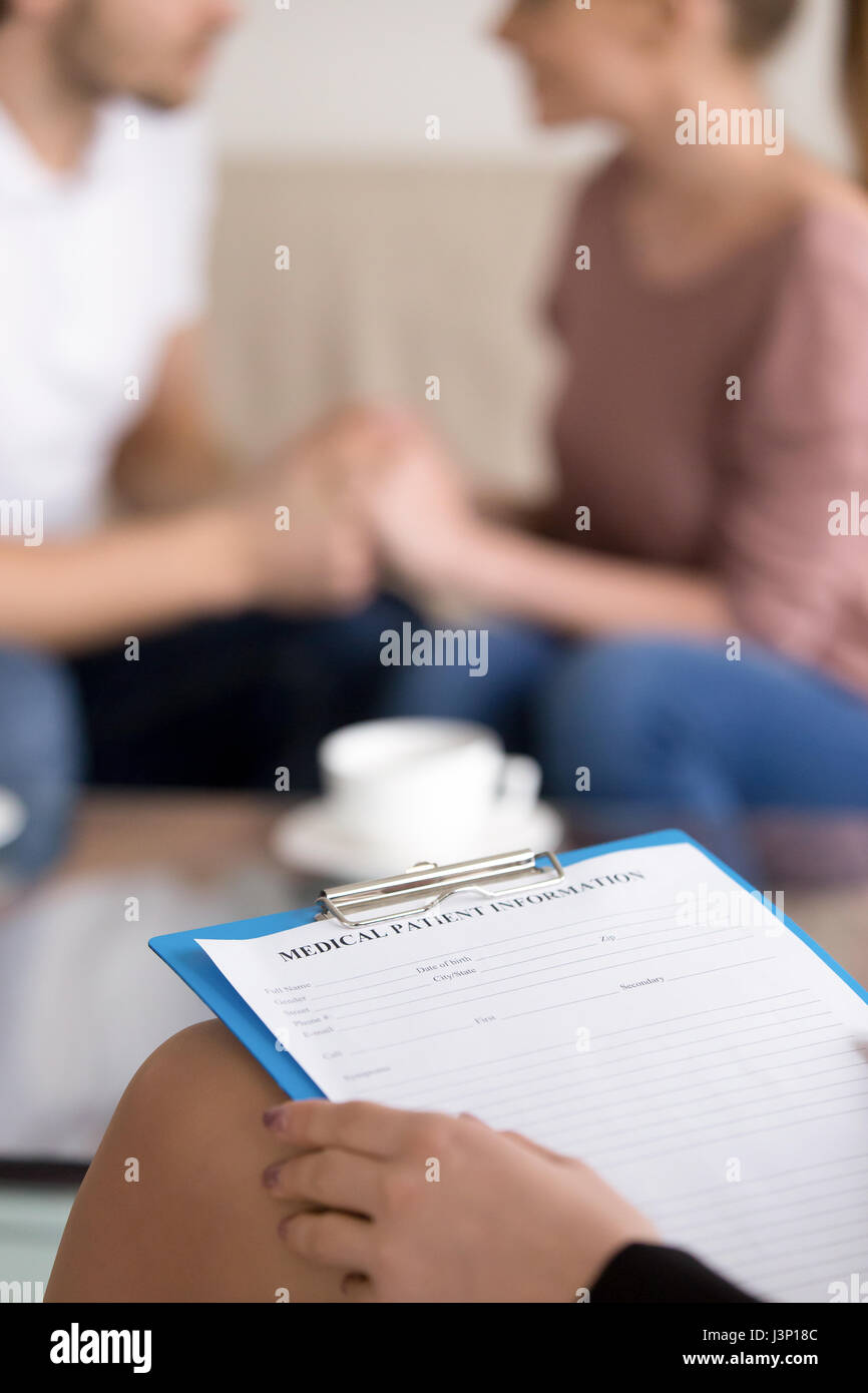 Couple counselling. Female psychotherapist with clipboard and ha Stock Photo