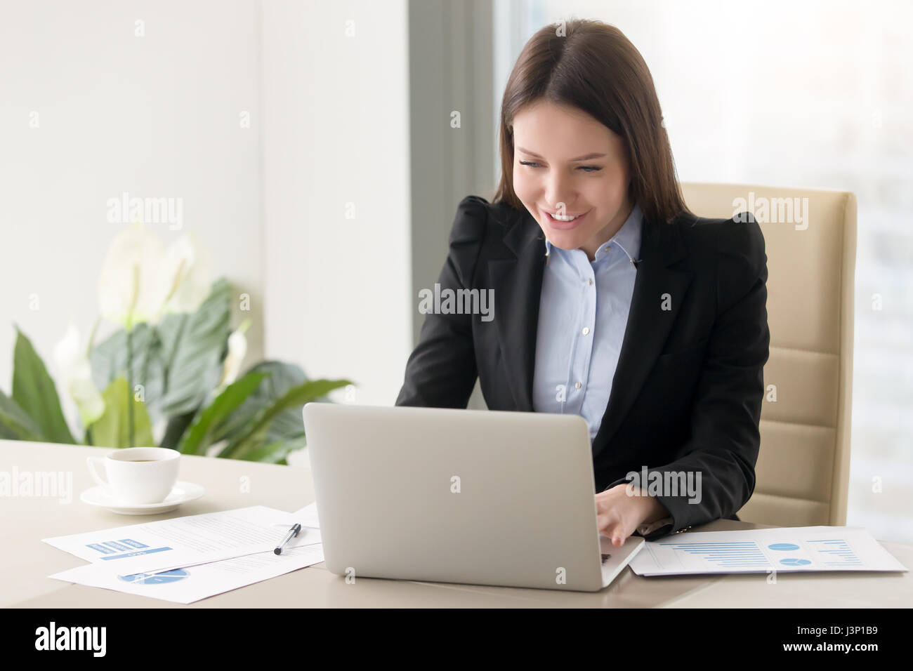 Smiling young business lady working with laptop, looking at scre - Stock Image