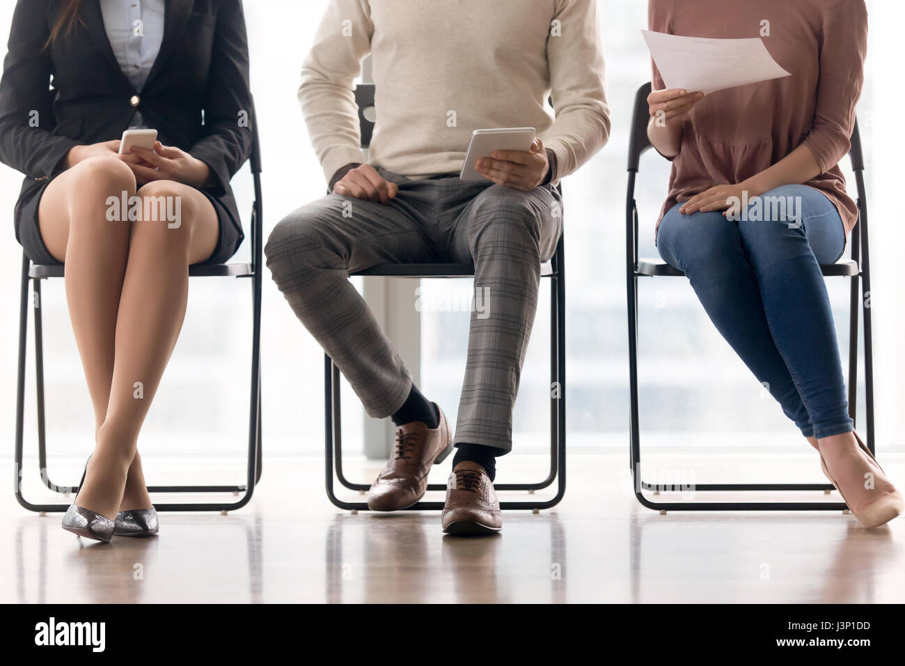 Group of people waiting for job interview, sitting on chairs - Stock Image