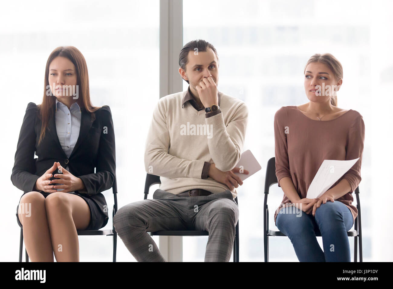 Business people group sitting on chairs waiting, expressing diff - Stock Image