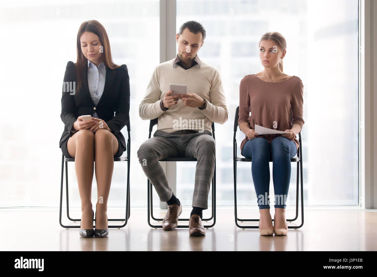 Bored people sitting on chairs waiting for a long time  - Stock Image