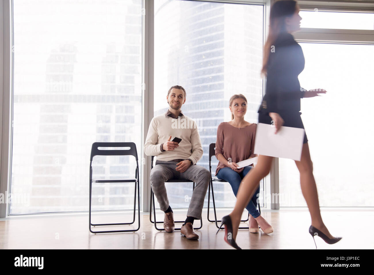 Job candidates gloating over female competitor walking after uns - Stock Image