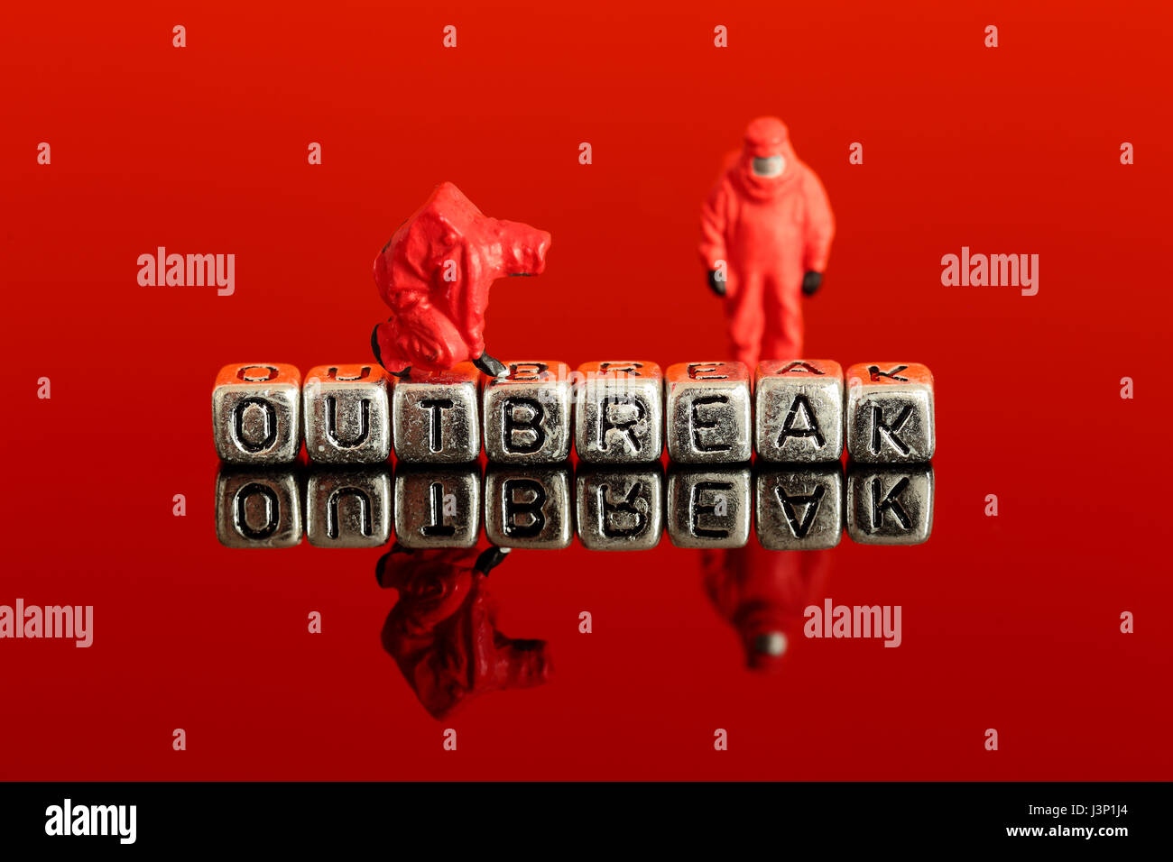 Miniature scale model team in chemical suits with the word outbreak on beads - Stock Image
