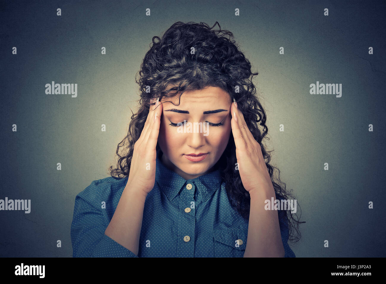 Closeup sad young woman with worried stressed face expression having headache isolated on gray wall background. - Stock Image