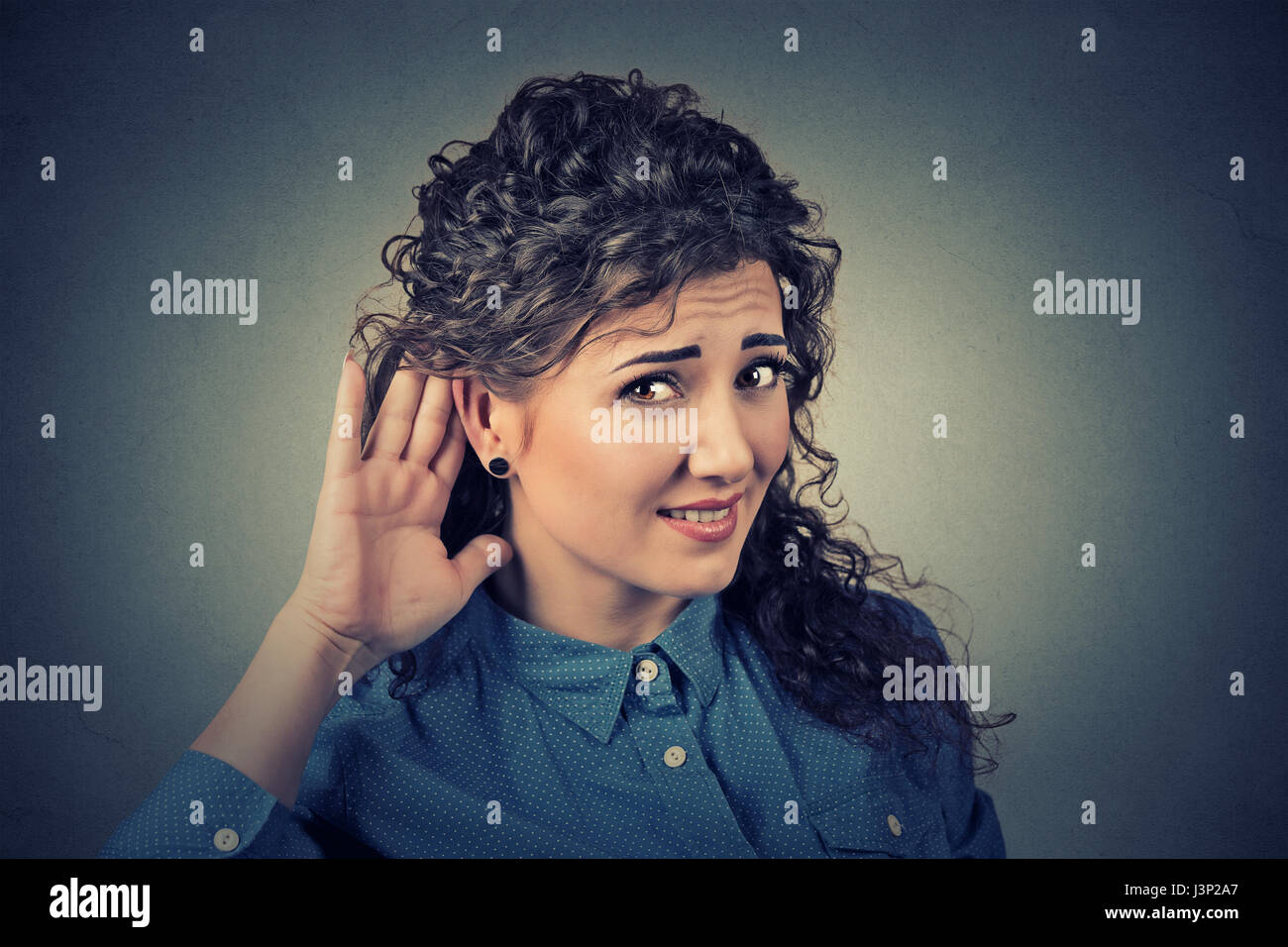 Closeup portrait of unhappy hard of hearing woman placing hand on ear asking someone to speak up or listening to - Stock Image