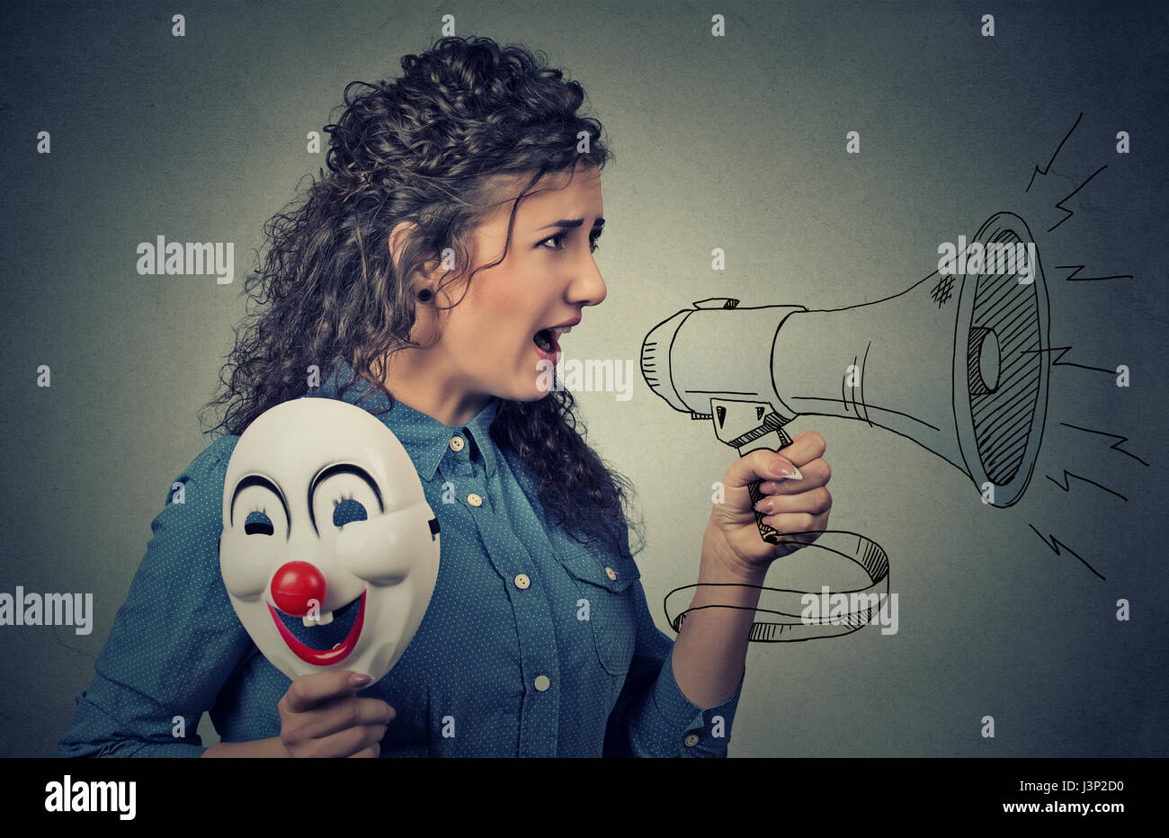 Woman with megaphone and clown mask screaming Stock Photo