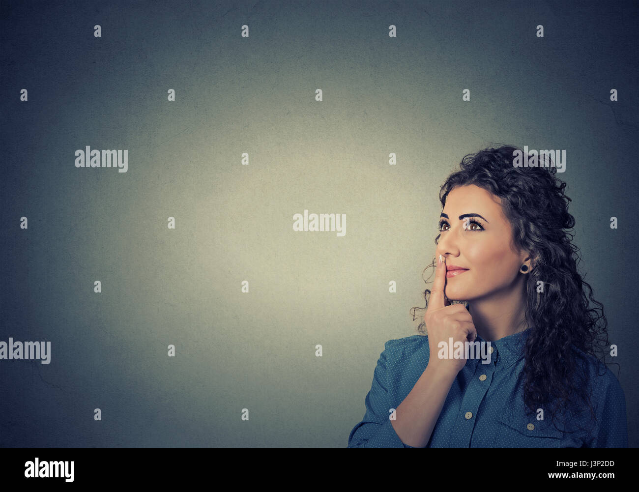 Portrait happy beautiful woman thinking looking up isolated on grey wall background with copy space. Human face - Stock Image