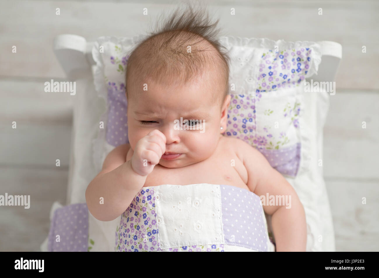 An overhead shot of a four month old, sulking, baby girl. She is lying in a tiny bed with quilted bedding. - Stock Image