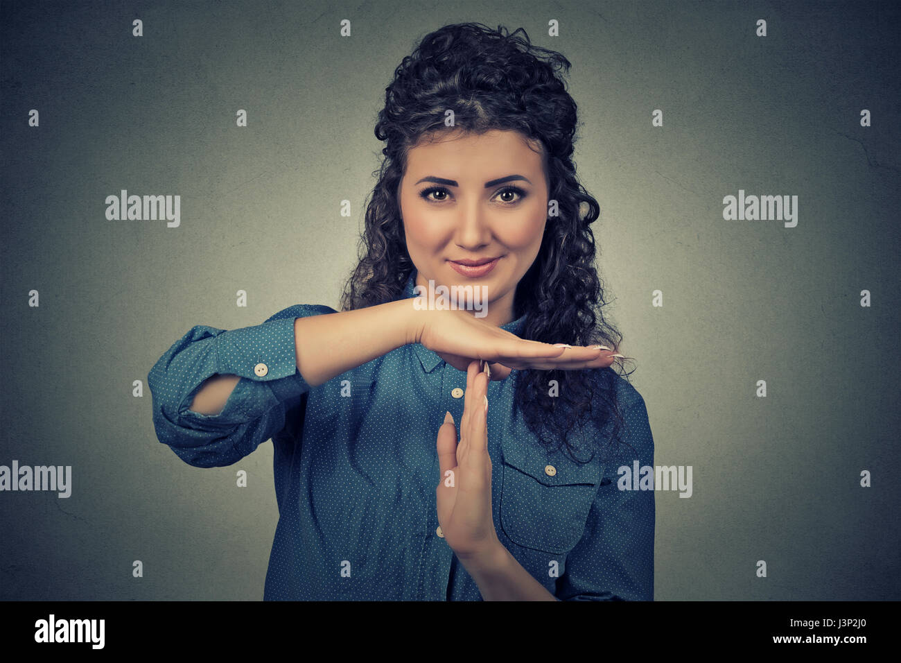 Closeup portrait, young, happy, smiling woman showing time out gesture with hands isolated on gray wall background. - Stock Image