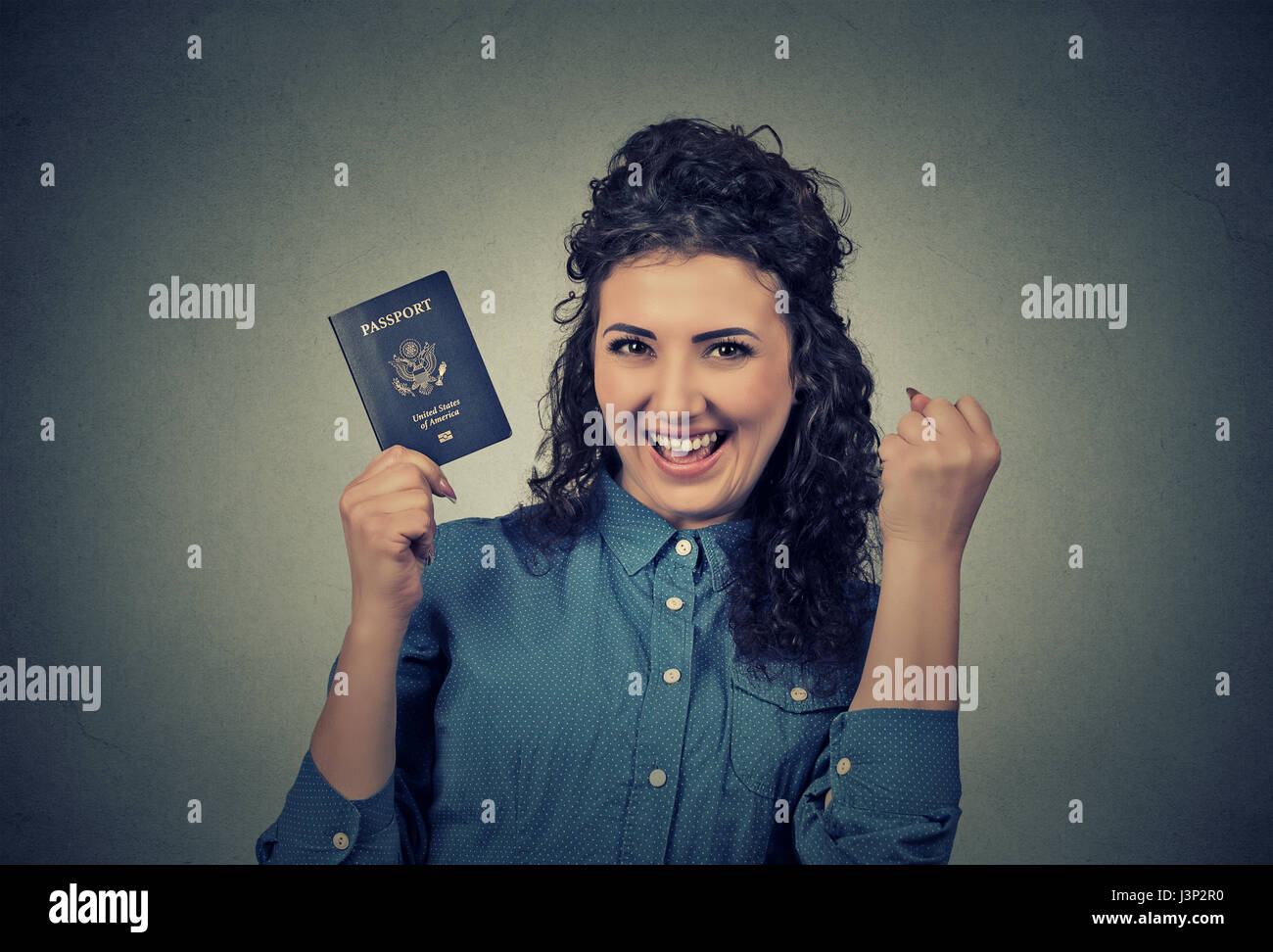 Portrait attractive young excited woman with USA passport isolated on gray wall background. Positive human emotions - Stock Image