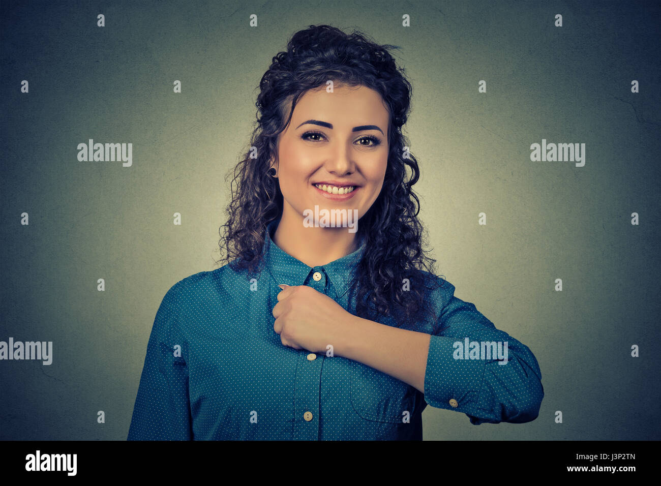 Superhero girl. Confident brave happy young woman isolated on gray wall background - Stock Image
