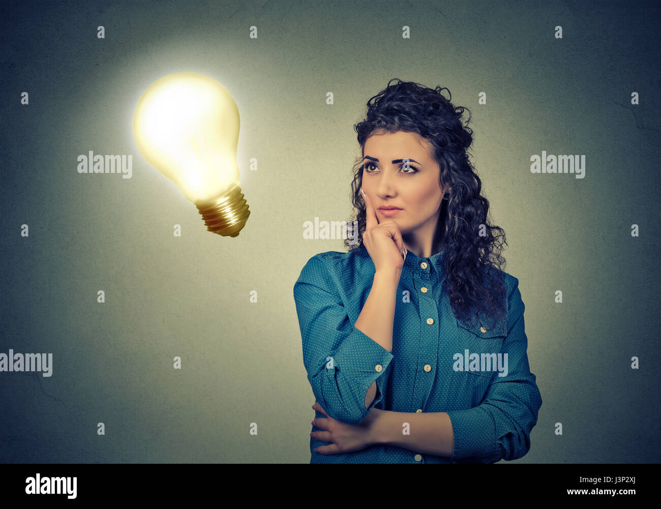 Closeup beautiful girl thinks looking up at bright light bulb isolated on gray wall background. Idea, education - Stock Image
