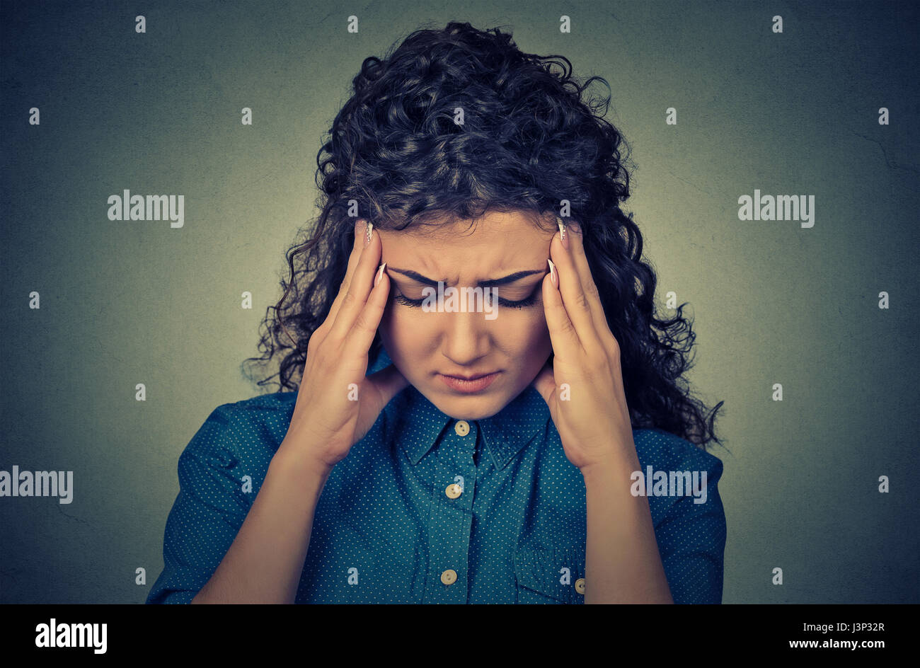 Closeup portrait worried sad young looking down isolated on gray wall background - Stock Image