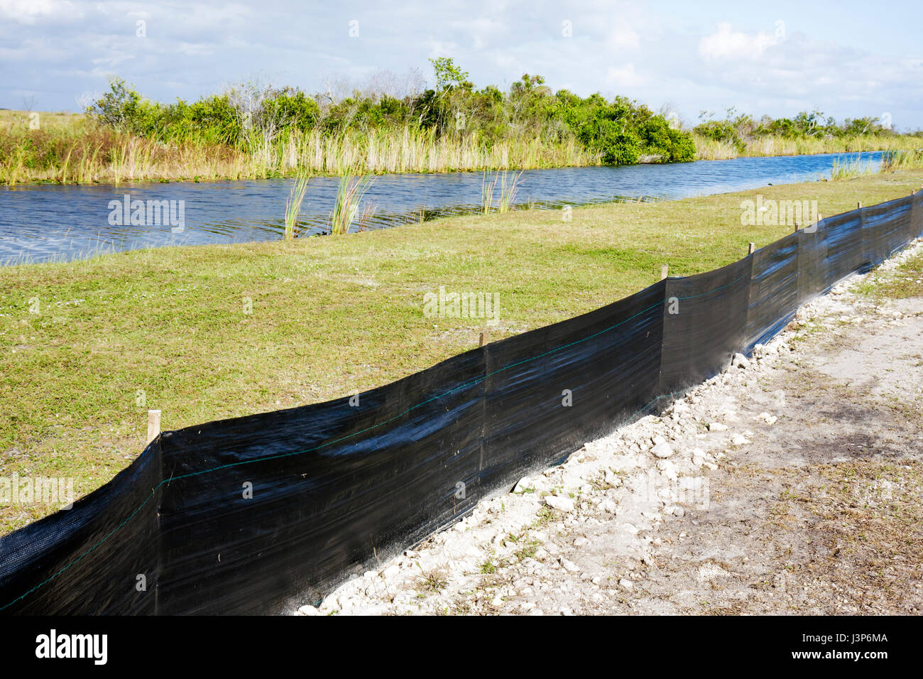 Florida The Everglades Tamiami Trail Shark River Slough construction dust barrier black plastic fence wetland canal Stock Photo