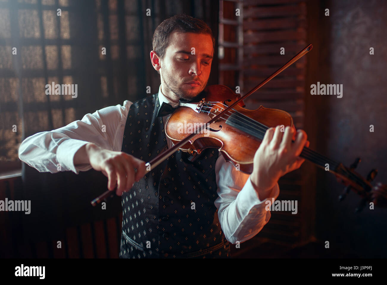 Male violinist playing classical music on violin. Fiddler man with musical instrument - Stock Image