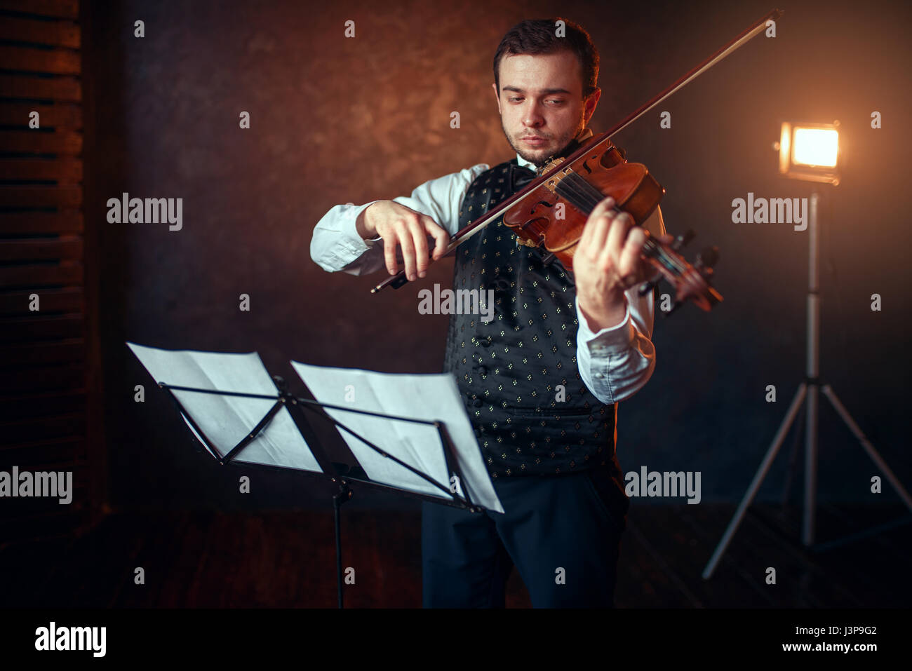 Portrait of male violinist with violin against music stand. Fiddler man with musical instrument playing in studio, - Stock Image