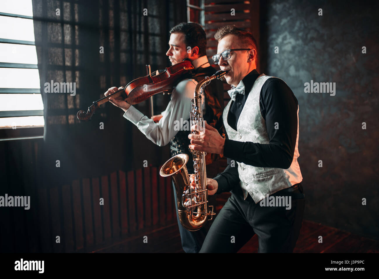 Sax man and fiddler duet playing classical melody. Jazz man and violinist - Stock Image