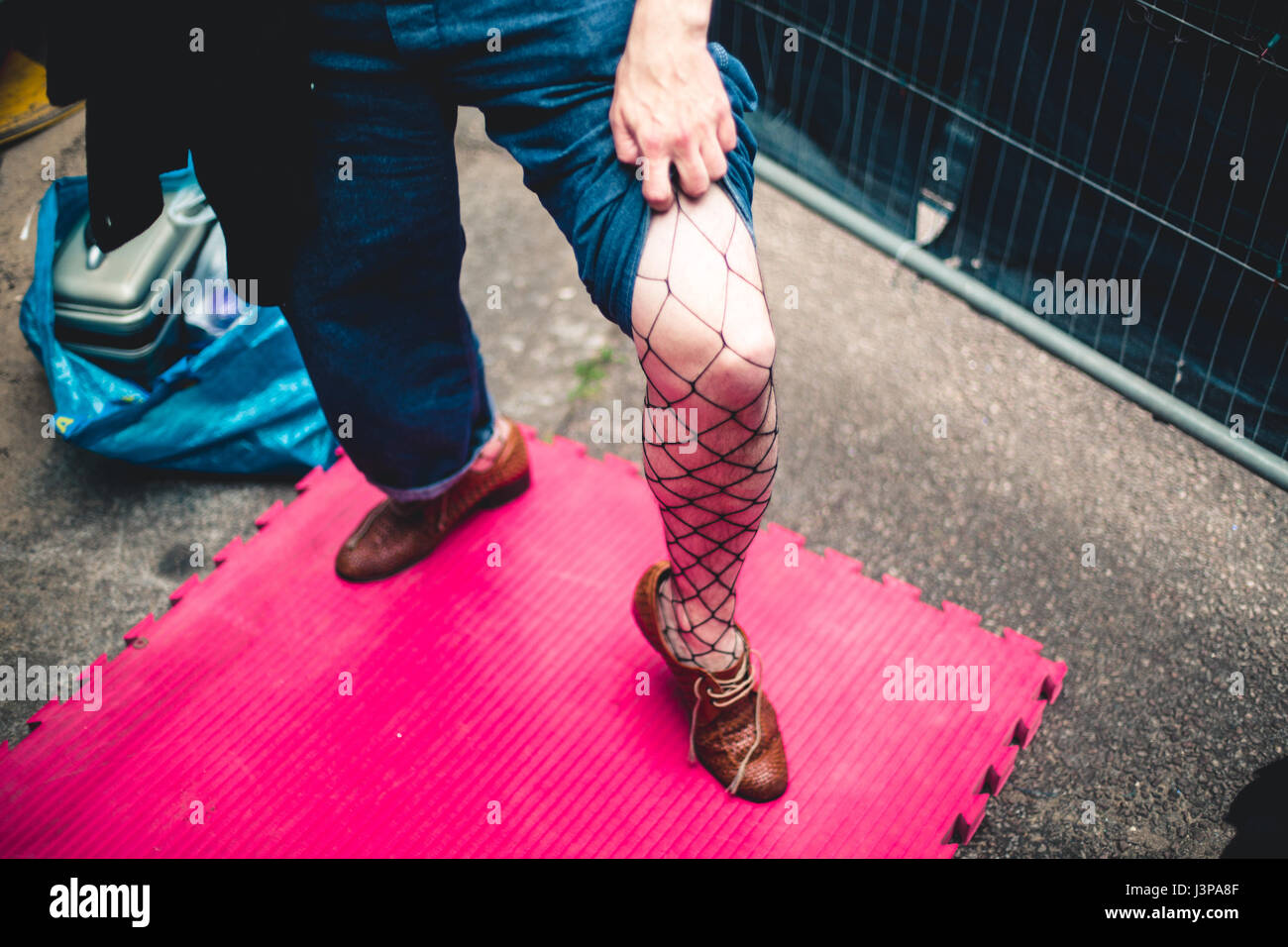 A male performer holds up his jeans to show his tights underneath. - Stock Image