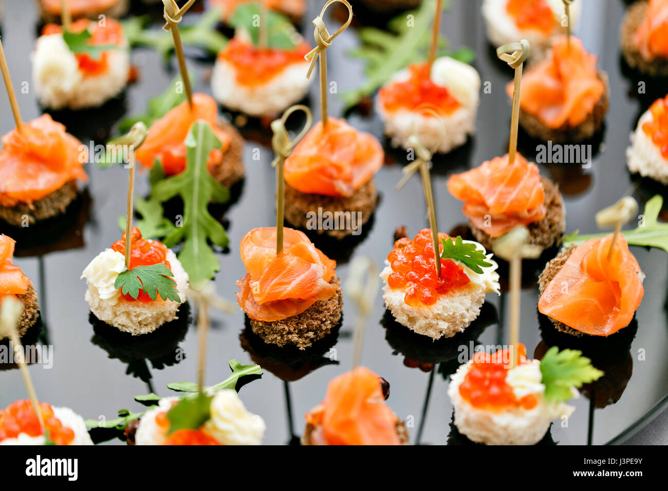 the buffet at the reception. Assortment of canapes. Banquet service. catering food, snacks with salmon and caviar. - Stock Image