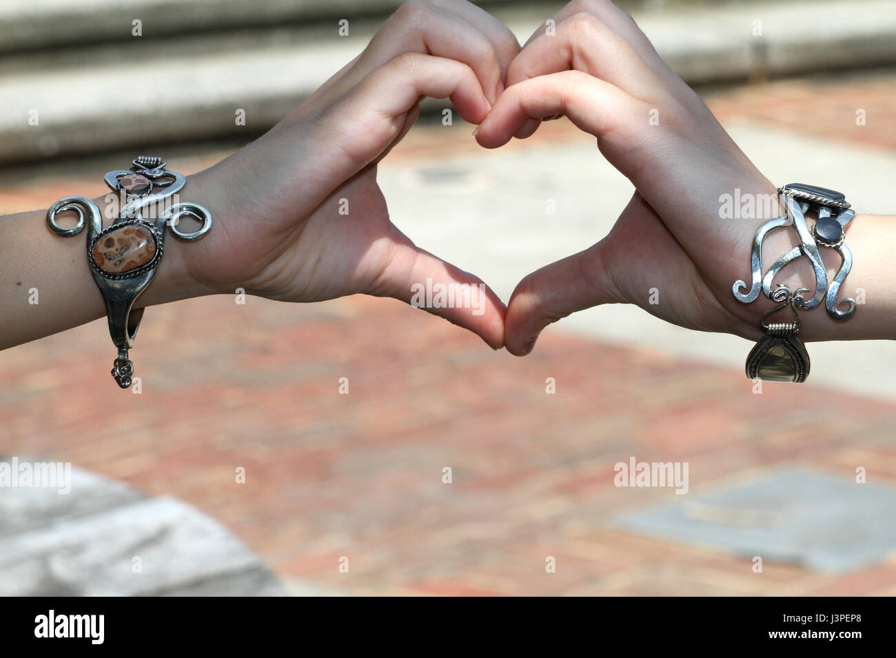 Two hands with metal bracelets shaping a heart - Stock Image